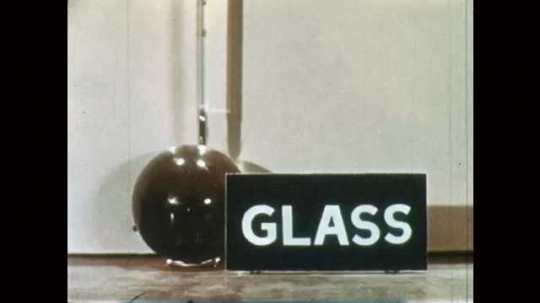 1950s: ball next to sign marked glass. arrows on thermometer indicate 30 and 40 degrees. wood globe goes from thirty to 35 on scale. light bulb sits at 29 on points.