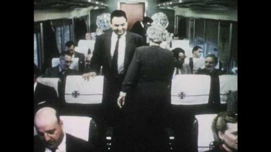 1950s: Men and women walk through chair car. Train attendant speaks to boy. Boy walks through crowded chair car. People sit in dome car.