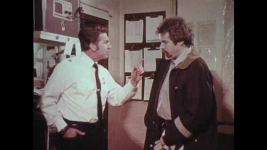 1970s: UNITED STATES: man points finger at member of staff. Fire men argue in station office