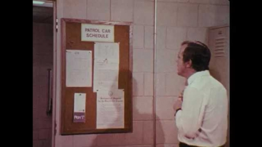 1970s: UNITED STATES: man looks at patrol car schedule on notice board. Men argue in locker room. Fire crew argue in station
