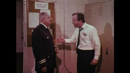 1970s: UNITED STATES: men argue in station office. Man shouts at boss. Man waves finger at employee. Side profile of man