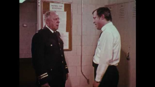 1970s: UNITED STATES: policemen shout at each other in station locker room. Man turns to colleague