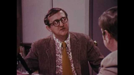 1970s: UNITED STATES: men speak at table in staff room. Men discuss paper.