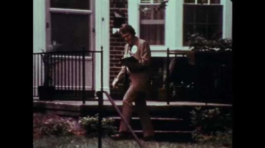 1970s: UNITED STATES: man walks on street. Man sees paper on floor