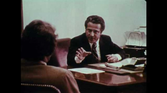 1970s: UNITED STATES: men speak in office. Men argue at desk. Man gestures with hands.
