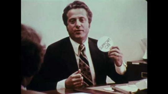 1970s: UNITED STATES: man throws badge. Man at office desk. Man gets annoyed at colleague