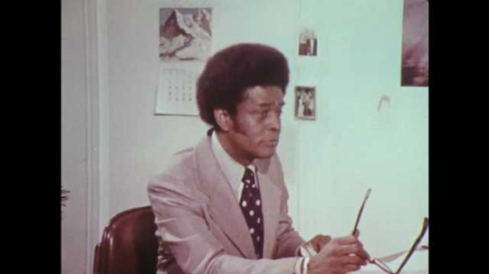 1970s: UNITED STATES: man sits at desk. Man waves glasses at colleague. Lady brings papers to desk. Men argue in office
