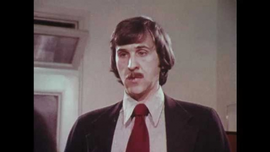 1970s: UNITED STATES: close up of man's face. Man in office argues with colleague
