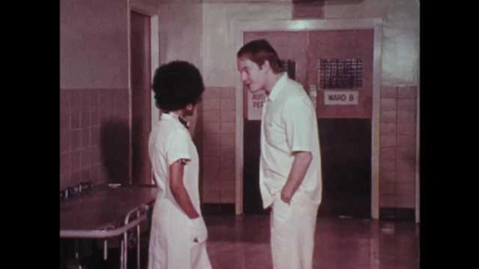 1970s: UNITED STATES: nurses argue in corridor of hospital. Lady talks to colleagues