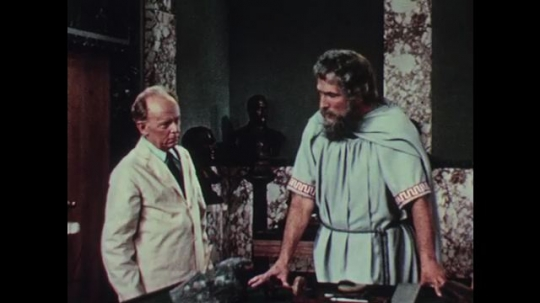 1950s: Man in white lab coat and tall, bearded man in robes have a conversation in museum storage room. Tall man points to artifacts on table.