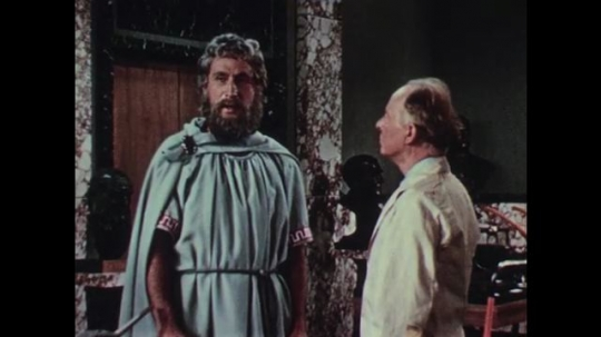 1950s: Tall, bearded man in robes and man in white lab coat have a conversation in museum storage room. Man fixing a tractor stops and talks.