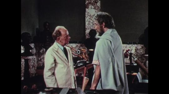 1950s: Man in white lab coat and tall, bearded man in robes have a conversation in museum storage room.