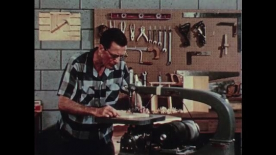 1950s: Man cuts wood on handsaw. Neighborhood road. Finger adjusts thermostat. Man turns knob on air-conditioner.