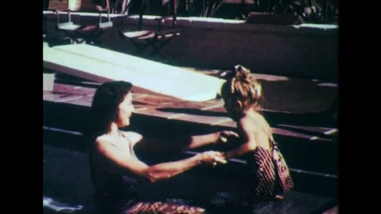 1950s: Woman and girl in pool. Man watches woman help girl in pool. Dissolve, man in field with gun.