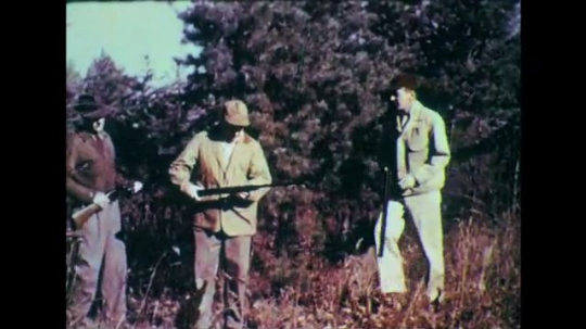 1950s: Men in woods, man approaches other man. Men correct man