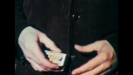 1950s: Close up, hands pull cartridges from pocket. Close up, warning on box. Animation, bullet trajectory from gun.