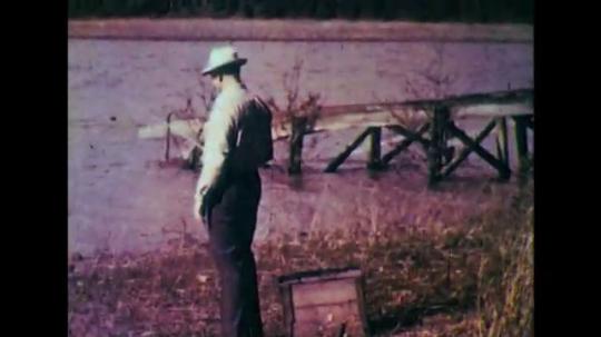 1950s: Quick pan to man fishing. Man stands, runs away.
