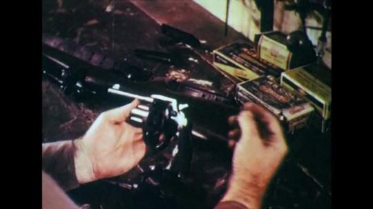 1950s: Hands put bullet into gun, pick up cartridge box.