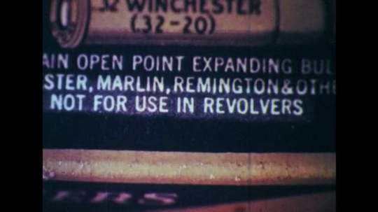 1950s: Close up of printed warning on box. Hands remove bullet from gun.