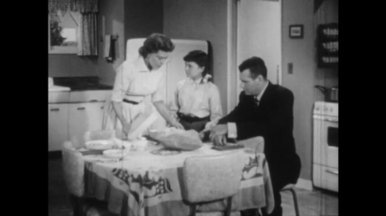 1950s: Man and woman sit at kitchen table, talk to young girl over open box and bag. Mother reaches to hold girl