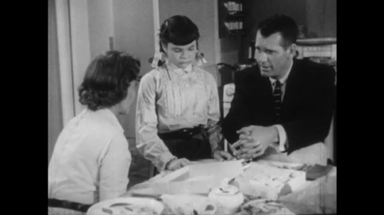1950s: Woman and man with young girl over kitchen table, man talks, hands clasped, takes daughter