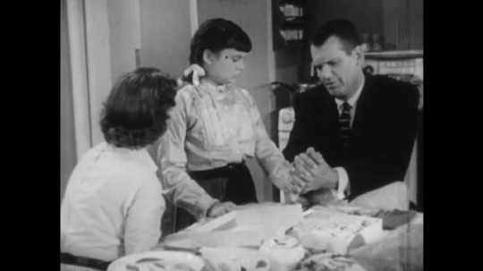 1950s: Woman and man with young girl over kitchen table, father with daughter
