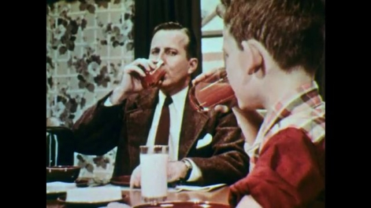 1950s: Man and child drinking juice. Young woman drinking juice. Middle aged man drinking juice. Two girls drinking juice. Several people of different ages and genders drinking juice.
