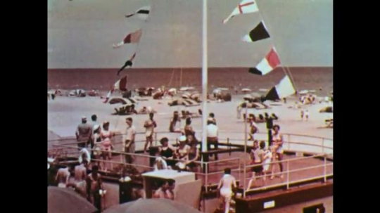 1950s: Beach full of people, flags in wind. More people at beach, playing in water. Drawing of body with sun to left.