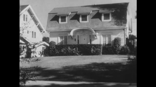 1950s: UNITED STATES: house and garden in sun. Man with briefcase leaves house. Man opens door. Man speaks to lady by stairs