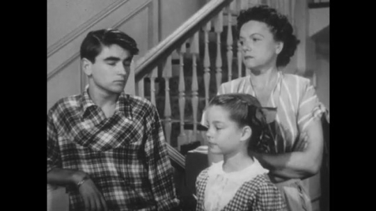 1950s: UNITED STATES: boy speaks. Lady looks at boy. Close up of man speaking. Man argues with family in hall
