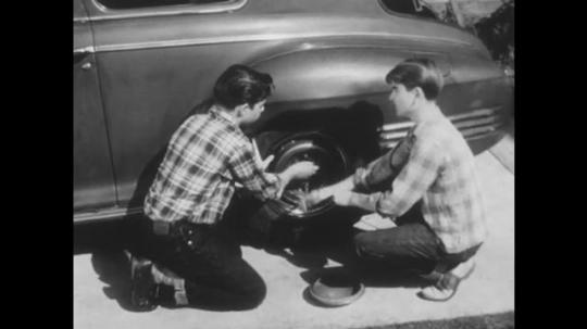 1950s: UNITED STATES: boys fix wheel on car. Boys speak. Boy removes tyre