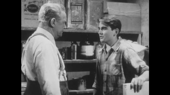 1950s: UNITED STATES: man speaks to boy in workshop. Boy argues with man. Boy tidies garage
