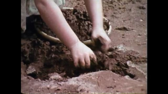 1970s: Girl digs into mudplie with dirty face. Girl chews dirty nails. Boy sits on tricycle and sucks his thumb. Cartoon worm makes its way up digestive tract. Cartoon worm swallows object.
