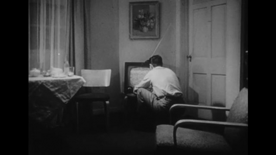 1950s: Husband kneels in front of television.  Man makes adjustments to tv.  Man pours a drink.  Man puts down drink.  Man sits in chair and watches tv.