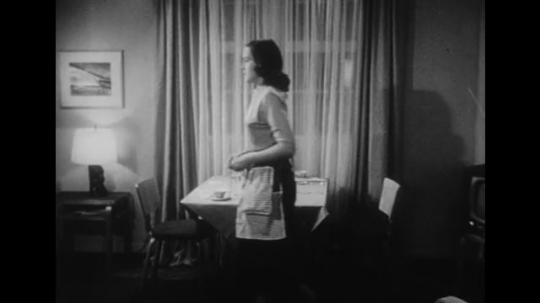 1950s: Wife walks away from table.  Wife serves dinner.  Husband rubs hands together and speaks.  Woman sits and eats soup.  Woman speaks.