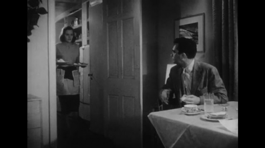 1950s: Wife brings plates of food from the kitchen and shuts door.  Woman serves meal.  Woman sits.  Husband eats and talks with his mouth full.