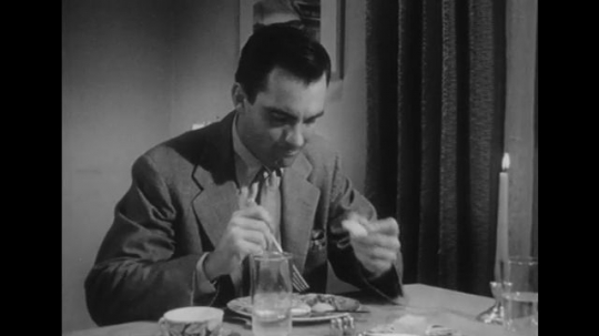 1950s: Husband sits at dinner table.  Man eats and talks.  Man and wife sit together.  Man smokes and smiles.  Man gestures.