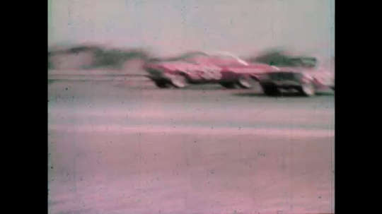1960s: Stock cars race around track.  Car skids and spins.  Daytona International Speedway.