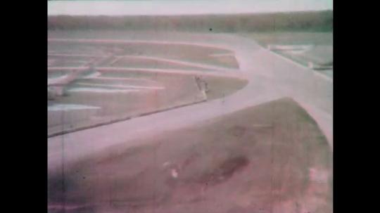1960s: Empty race track.  Garages.  Work benches in garage.  Men work on cars in garage.