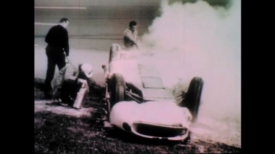 1960s: Fire is extinguished after race car flips.  Race car drivers stand together.  Side of race car.  Man stands and speaks.