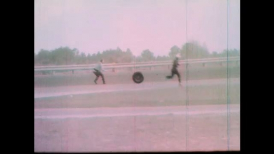 1960s: Tire rolls down race track.  Man catches and rolls tire.  Men examine wreckage.  Damaged parts thrown in pile.  Marching band conductor waves arms.