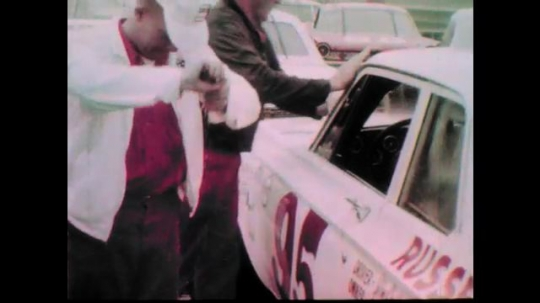 1960s: Men dry off race cars.  Men wring out wet rags.  Men stand in large group and talk.