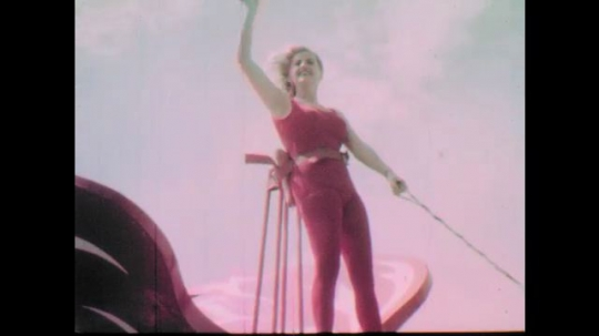 1960s: Woman rides on parade float down race track.  Man uses and lowers movie camera.