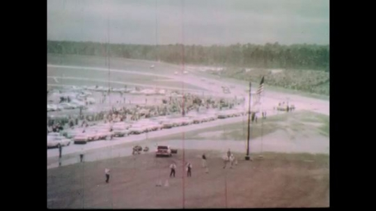 1960s: Race cars move onto track.  Red and yellow lights blink.  Cars circle track.