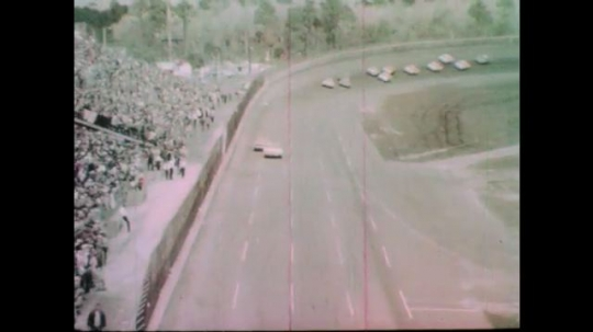1960s: Race cars speed down track.  Two cars take the lead.  Spectators watch.