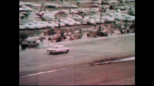 1960s: Car pulls onto pit road.  Race cars speed down track.