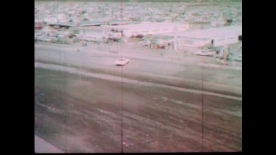 1960s: Race car spins to a stop on pit road.  Crew approaches car.  Firefighter stands nearby.  Race cars speed down track.