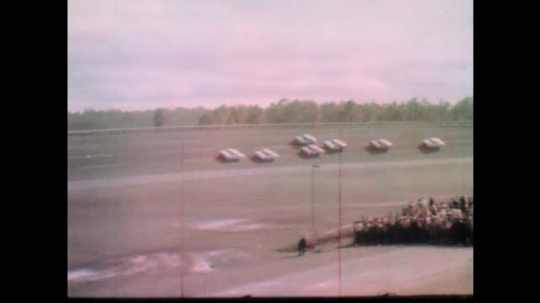 1960s: Race cars speed down track.  Cars drive past grandstand.