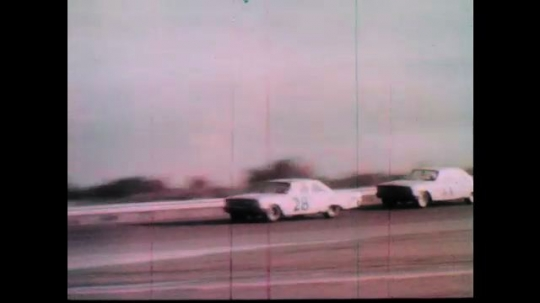 1960s: Race cars speed down track.  Cars follow closely.