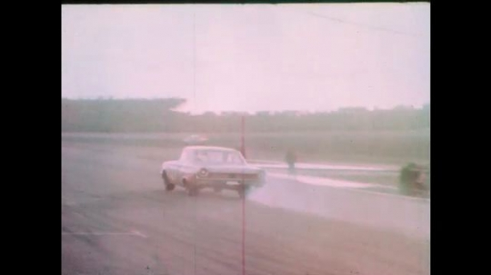 1960s: Race car speeds down pit road.  Spectators stand.  Cars drive down track.  Scoreboard.